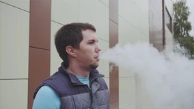 Young man smoking e-cigarette on the street, vape slow motion stock video footage
