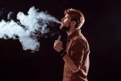 Young man smoking electronic cigarette Royalty Free Stock Photos