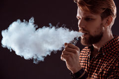 Young man smoking electronic cigarette Royalty Free Stock Photos
