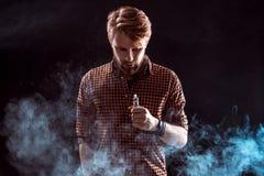 Young man smoking electronic cigarette Royalty Free Stock Image