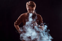 Young man smoking electronic cigarette Stock Photo