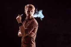 Young man smoking electronic cigarette Royalty Free Stock Images