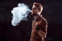 Young man smoking electronic cigarette Royalty Free Stock Image