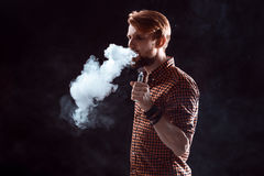 Young man smoking electronic cigarette Stock Photography