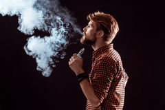 Young man smoking electronic cigarette Royalty Free Stock Photo