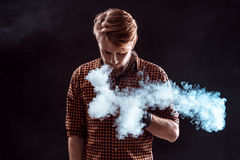 Young man smoking electronic cigarette Stock Images