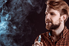 Young man smoking electronic cigarette Royalty Free Stock Photography