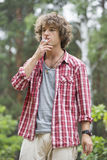 Young man smoking in forest Stock Photography