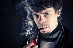 Young man smoking a pipe Stock Photos