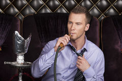 Young man smoking shisha in restaurant. Royalty Free Stock Photography