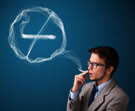 Young man smoking unhealthy cigarette with no smoking sign Royalty Free Stock Images