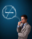Young man smoking unhealthy cigarette with no smoking sign Royalty Free Stock Image