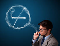 Young man smoking unhealthy cigarette with no smoking sign Stock Photo