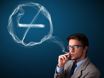 Young man smoking unhealthy cigarette with no smoking sign stock photography