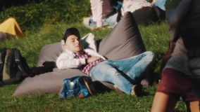 Young man in snapback chilling out laying on a bean bag outside in a park stock video
