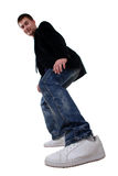 Young man in sneakers. Young man in a black jacket and sneakers on a white background Royalty Free Stock Photo