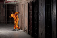 Young Man Sneaking Out of Prison. A young african american man with an afro is sneaking out of a prison cell. Vertical shot Stock Photos