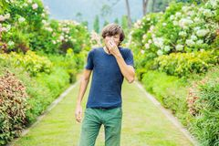 Young man sneeze in the park against the background of a flowering tree. Allergy to pollen concept stock photo