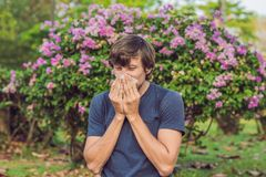 Young man sneezes because of an allergy to pollen stock image