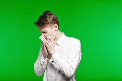 Young man sneezing and running nose Stock Images
