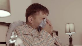 Young man sneezing and using his handkerchief to blow his nose stock footage