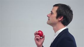 Young man sniffing an apple stock footage