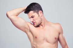 Young man sniffing his armpit. Handsome young man sniffing his armpit over gray background Royalty Free Stock Photos