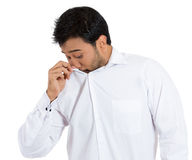 Young man sniffing his own shirt to check if he is stinking Royalty Free Stock Photography