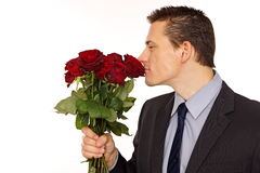 Young man sniffs scent of roses Stock Photo