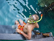 Young man snorkeling in clear shallow tropical sea. Over coral reefs royalty free stock photos
