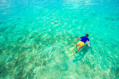 Young man snorkeling in clear tropical turquoise Royalty Free Stock Photo
