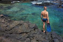 Young man with snorkeling equipment on the rock coast Stock Image