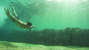 Young Man Snorkeling and Floating Through the Frame, Underwater View in Red Sea, Egypt. Man dives into the depths of the blue water, with a mask and a tube stock footage