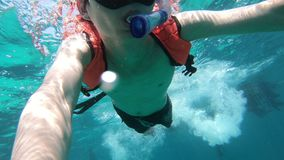 Young man snorkeling and free diving underwater GoPro selfie.  stock video