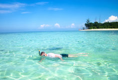 Young man snorkeling next to tropical island. Young man snorkeling next to a beautiful tropical island Royalty Free Stock Images