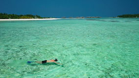 Young man snorkeling in tropical lagoon with over water bungalows. On Maldives island stock video footage