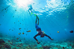 Young man in snorkelling mask dive underwater. Happy family vacation. Man in snorkeling mask with camera dive underwater with tropical fishes in coral reef sea Stock Images