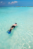 Young man snorkling in tropical lagoon with over water bungalows Royalty Free Stock Image