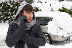 Young man in snow with broken down car. On the phone Royalty Free Stock Image