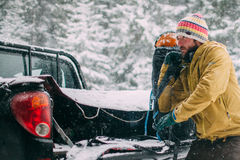 Young man in the snow forest raises backpack. From the car Stock Photography