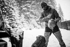 Young man in the snow forest shake off snow from helmet. Winter Royalty Free Stock Image