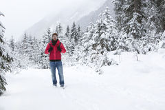 Young man with snow glasses hiking in wintry forest landscape Stock Photography