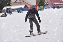 Young man on snowboard downhill with people in the background Royalty Free Stock Photos