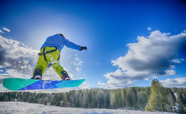 Young man on the snowboard. Jumping over the slope in winter stock photos