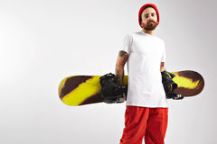 Young man with a snowboard in studio stock images