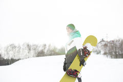 Young man with snowboard walking in snow Royalty Free Stock Photos