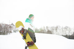 Young man with snowboard walking in snow Royalty Free Stock Photo