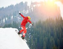 Young man snowboarder jumping from the top of the snowy hill with snowboard in the evening. At sunset at winter ski resort. Ski season and winter sports concept Stock Photo