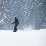 Young man snowboarding down a slope Stock Images