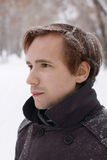 Young man with snowflakes in hair looks at distance. Outdoor at winter snowy day Royalty Free Stock Images